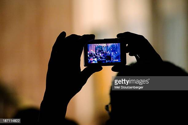 Parent in the audience uses a smart phone to video record the school's yearly Christmas play.