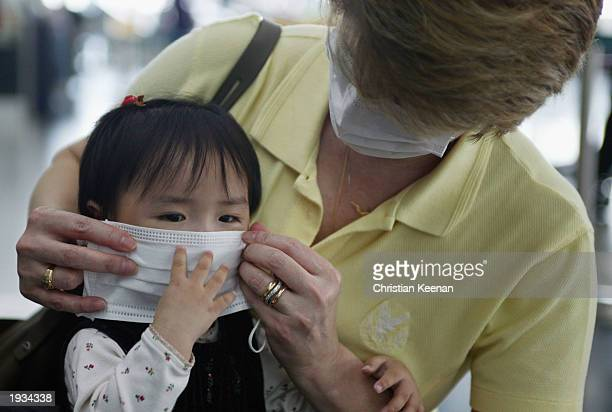 Parent puts on a protective mask before boarding a flight to the US at Chek Lap Kok airport April 16, 2003 in Hong Kong, China. Cathay Pacific...
