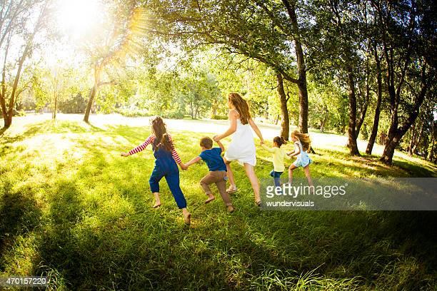 Parent running with kids through a sunlit park