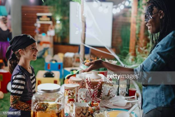 parent serving candy and popcorn to her kids and their friends at backyard movie night - scaredastronaut stock pictures, royalty-free photos & images