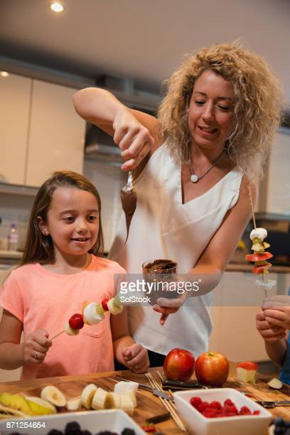 Parent serving chocolate spread to female child.