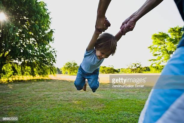 Parent spinning little boy in park