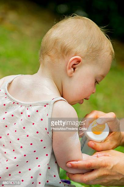 Parent spraying sunscreen on babys arm