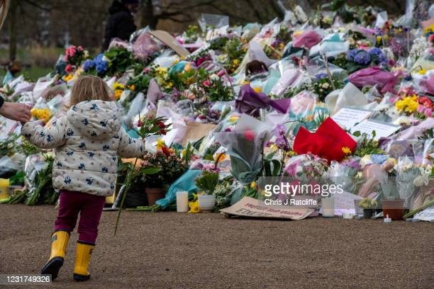 Parent takes daughter to leave a floral tribute at Clapham Common bandstand where people continue to pay their respects to Sarah Everard on March 16,...