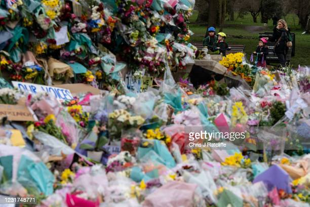 Parent takes their children to look at floral tributes left at Clapham Common bandstand where people continue to pay their respects to Sarah Everard...