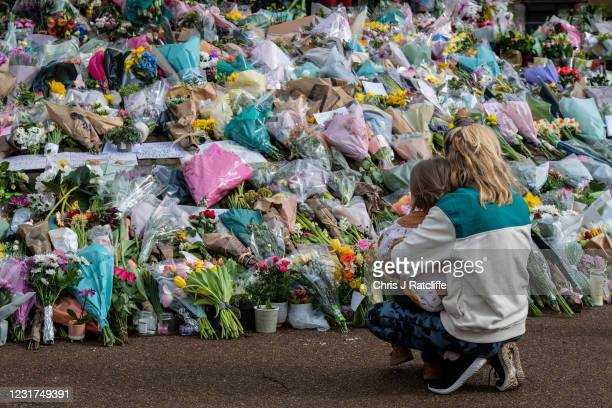 Parent takes their daughter to look at floral tributes left at Clapham Common bandstand where people continue to pay their respects to Sarah Everard...