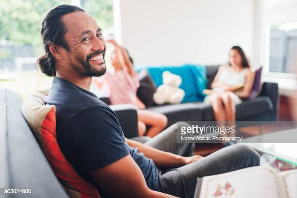 parent talking each other while kids sitting on sofa playing. - candid stock pictures, royalty-free photos & images