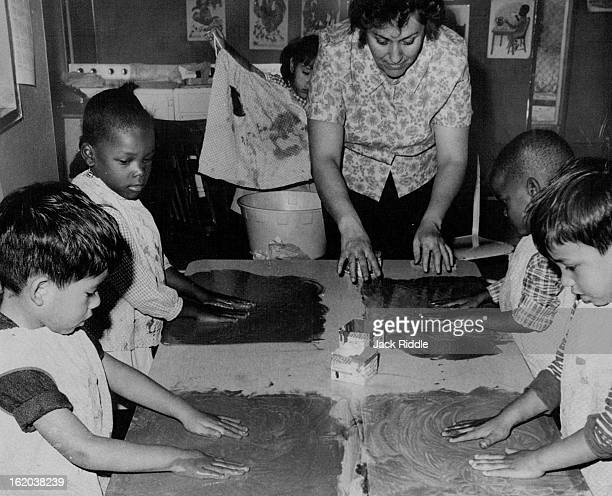 OCT 5 1968 OCT 10 1968 Parent Volunteer Teacher Mrs Josie Cosio shows youngsters how to paint at Curtis Center Children are from left Raymond...