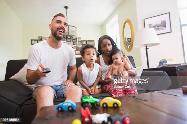 parent watching television with son and daughter - white wife black baby stock photos and pictures