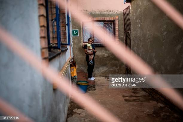 A parent with children stands inside the Childcare Orientation Centre in Klipspruit West in Soweto on March 13 2017 Nine children under the age of...