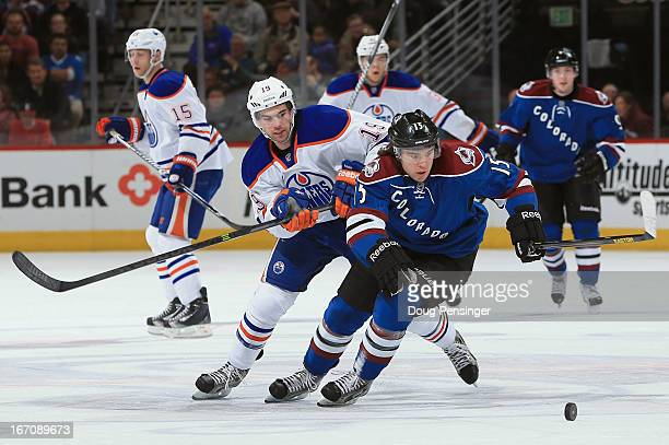 A Parenteau of the Colorado Avalanche and Justin Schultz of the Edmonton Oilers pursue the puck during first period action at the Pepsi Center on...