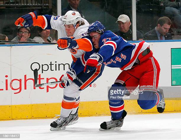 A Parenteau of the New York Islanders is covered by Milan Jurcina of the New York Rangers in the first period of an NHL hockey game at Madison Square...