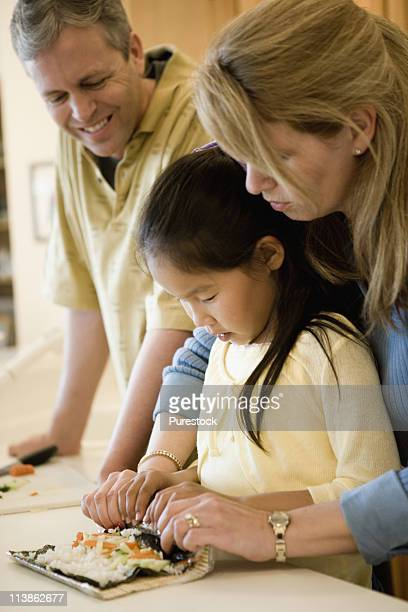 Parents and adopted daughter making sushi