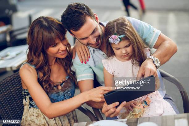 Parents and adorable daughter with digital tablet in cafe