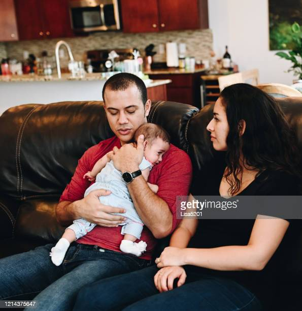 parents and baby sitting on the couch in the living room, candid young family togetherness at home - puerto rican ethnicity stock pictures, royalty-free photos & images