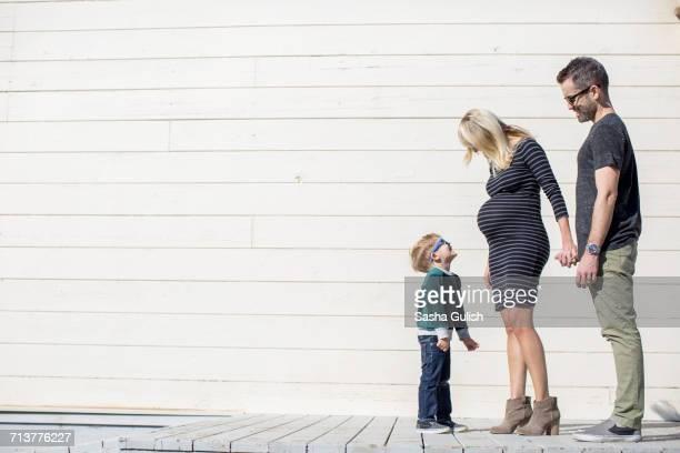 parents and boy beside wooden building - bottines photos et images de collection