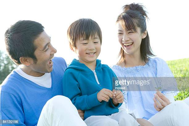 Parents and boy relaxing on graas, laughing