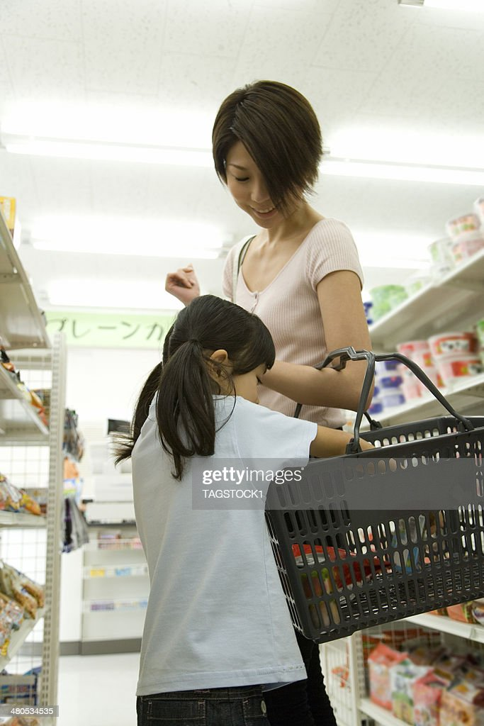 Eltern und Kinder, die einige Einkaufsmöglichkeiten im Supermarkt : Stock-Foto