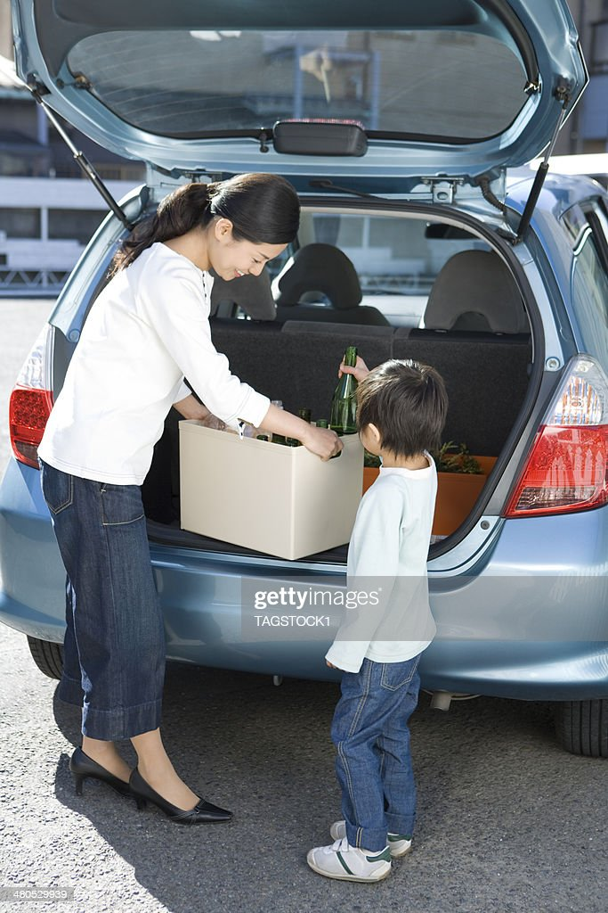 Parents and child loading empty bottles on car : Stock Photo