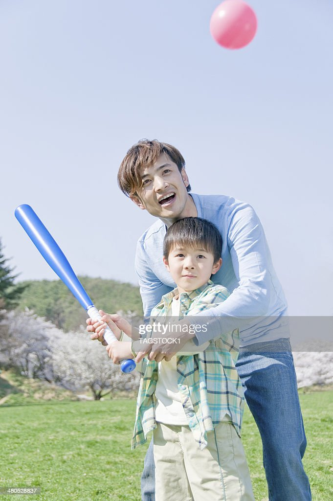 Parents and child playing baseball : Stock Photo