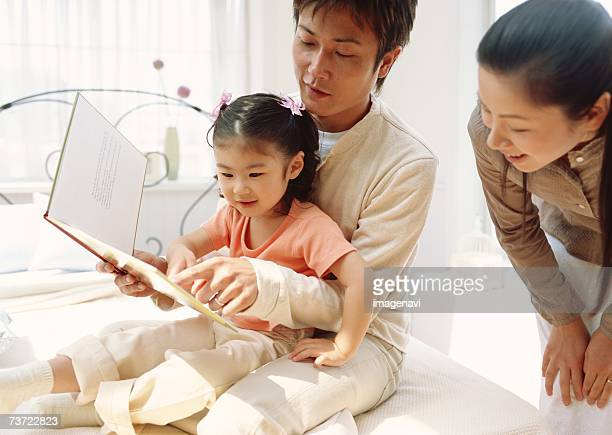 Parents and child reading a picture book