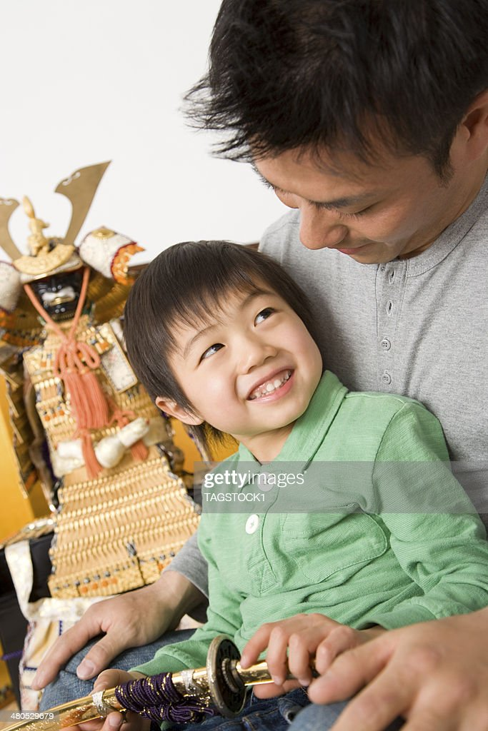 Parents and child sitting in front of May doll : Foto stock