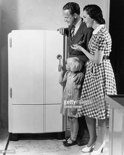 Parents and Child Stand Next to Refrigerator