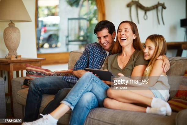 parents and child streaming media content from a digital tablet. - family at home stock pictures, royalty-free photos & images