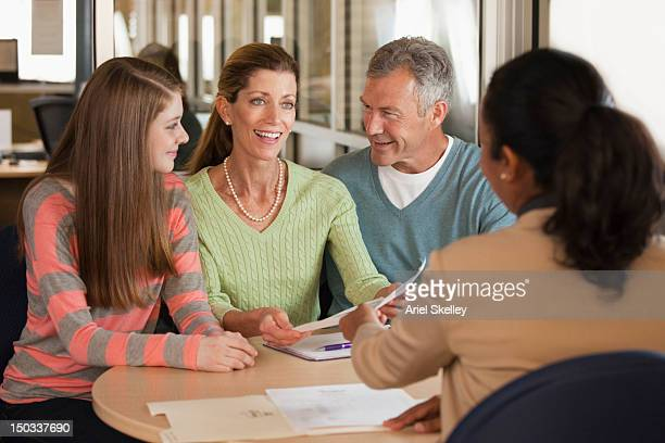 parents and child talking to financial advisor - college application stock photos and pictures