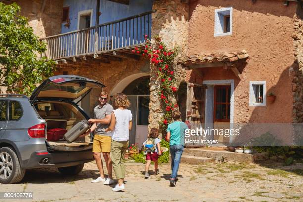 parents and children by car outside house - arrival stock pictures, royalty-free photos & images