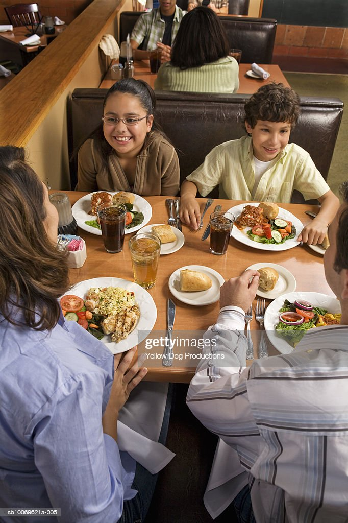 Parents and children (8-10) dinning in restaurant, high angle view : Stock Photo
