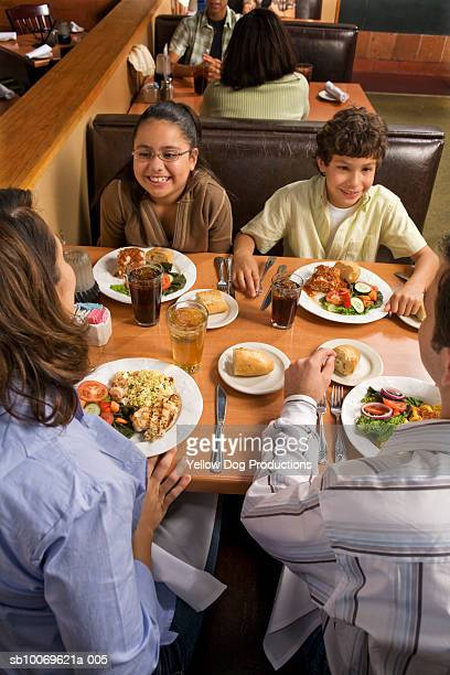 parents and children (8-10) dinning in restaurant, high angle view - dog eats out girl stock pictures, royalty-free photos & images