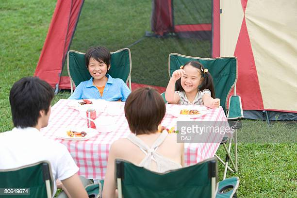 Parents and children eating kebabs, smiling, summer