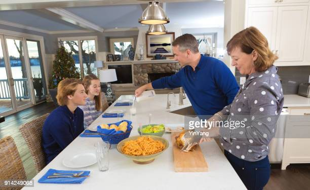 parents and children family lunch meal in kitchen counter - stereotypically middle class stock photos and pictures