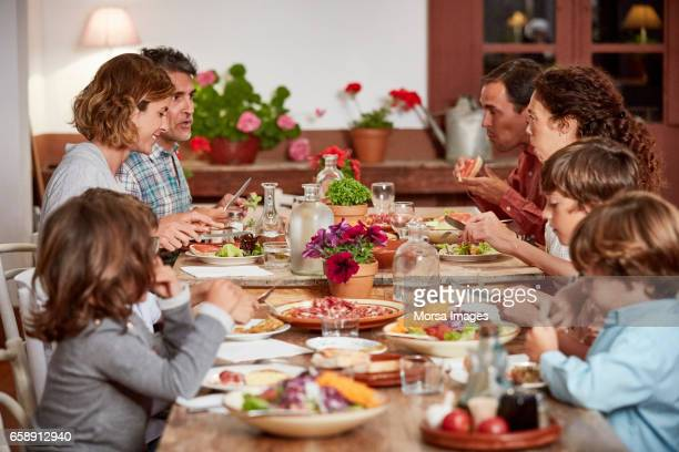 Parents and children having food at dining table