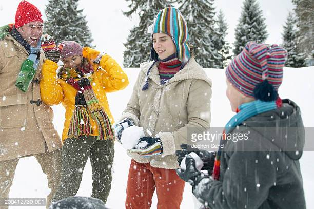 Parents and children (9-13) having snowball fight