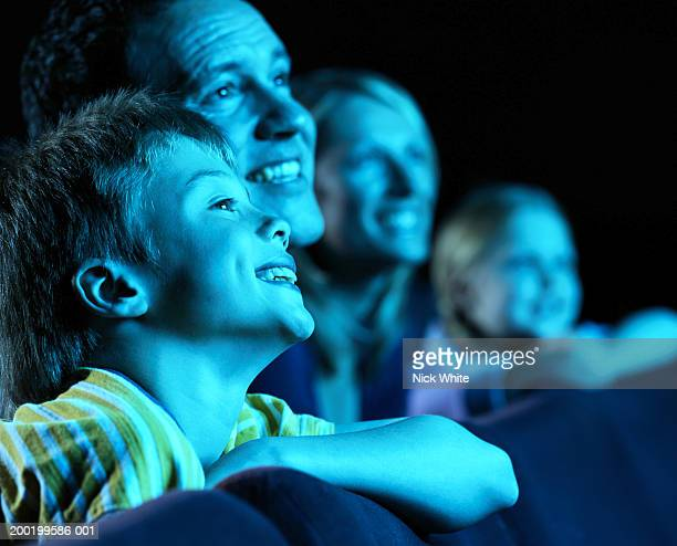 Parents and children (8-10) in cinema, smiling (focus on boy)