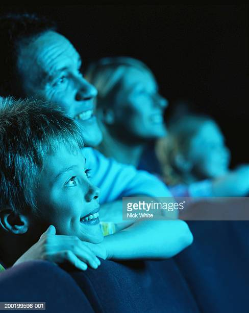 parents and children (8-10) in cinema, smiling (focus on boy) - blue film video stock photos and pictures
