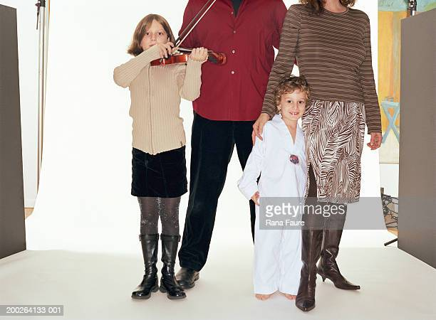 Parents and children (3-9) in studio, portrait, girl with violin