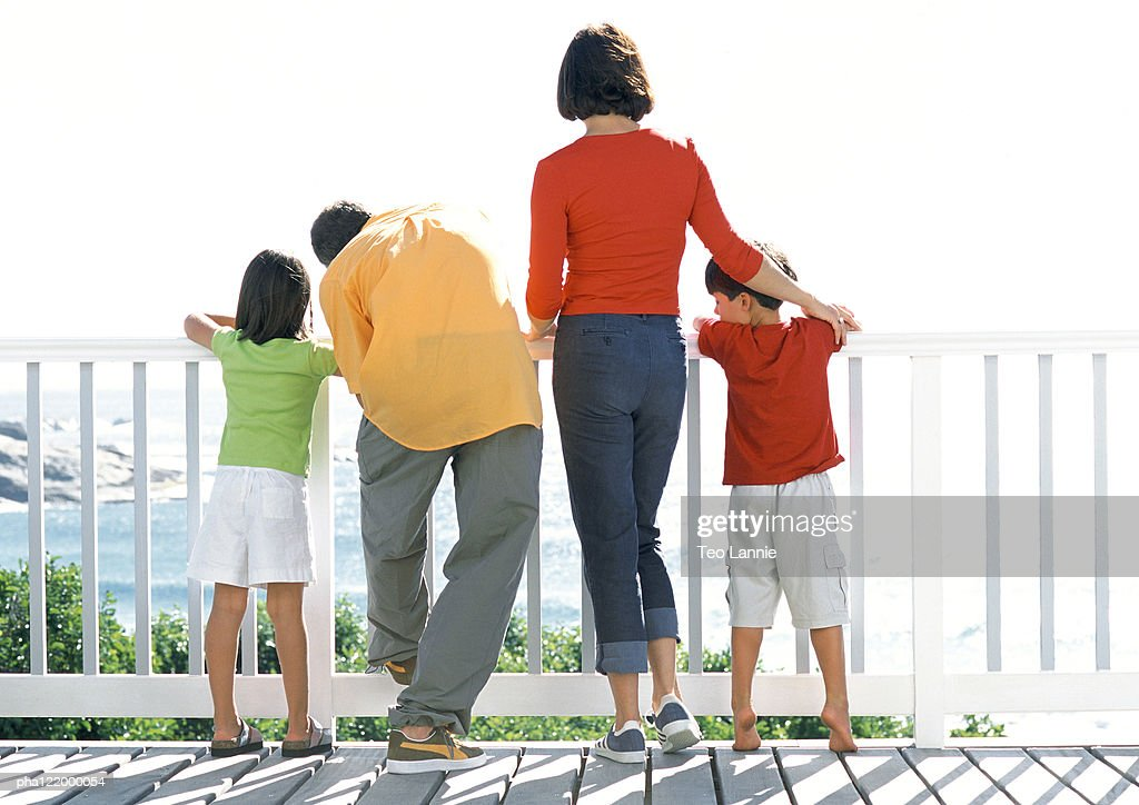 Parents and children looking out to sea, rear view : Stockfoto