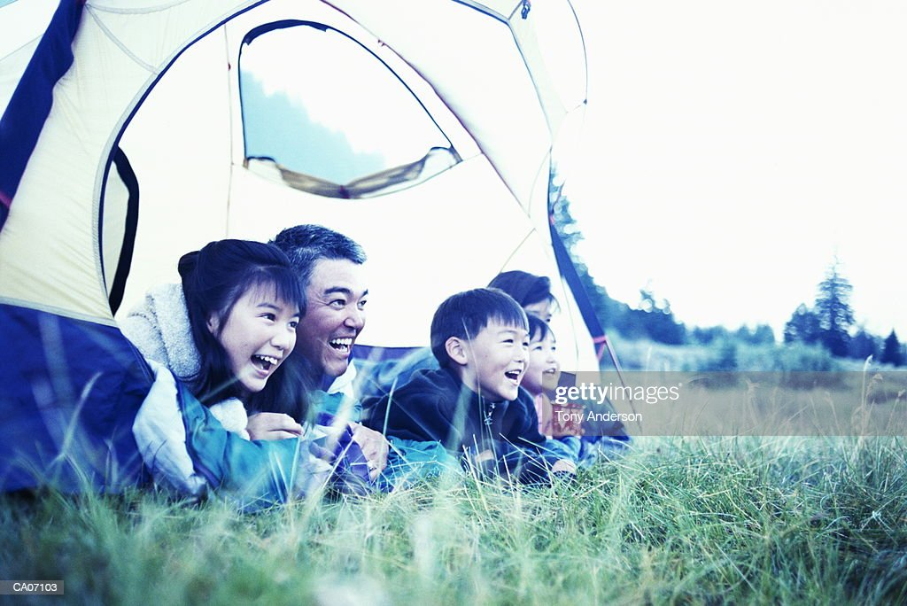 Parents and children (5-11) lying on sleeping bags in tent, laughing : ストックフォト
