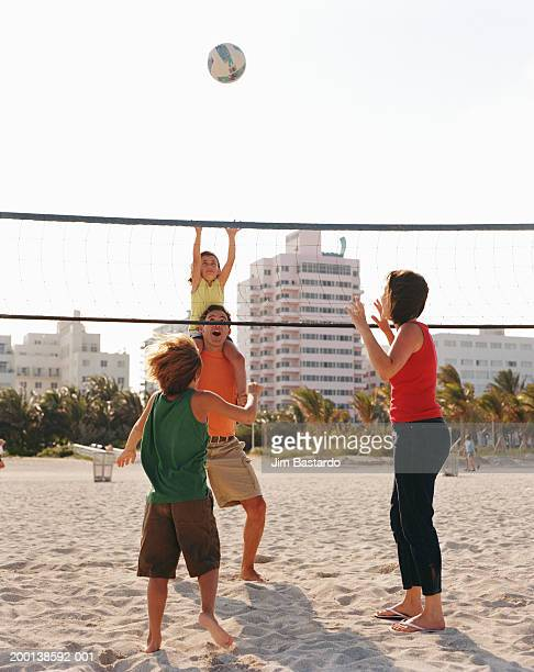 parents and children (5-9) playing volleyball at beach - beach volley photos et images de collection