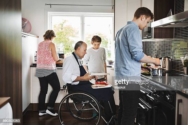 Parents and children preparing food together in kitchen