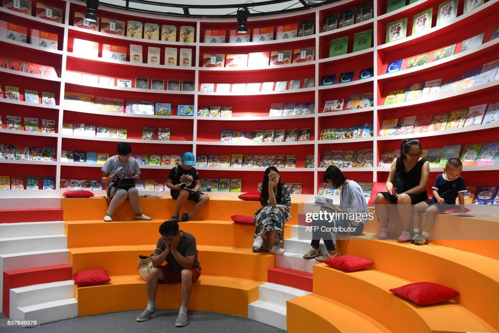 Parents and children read books at a stand at the Beijing International Book Fair in Beijing on August 23, 2017. The book fair runs from August 23 to 27. / AFP PHOTO / Greg Baker