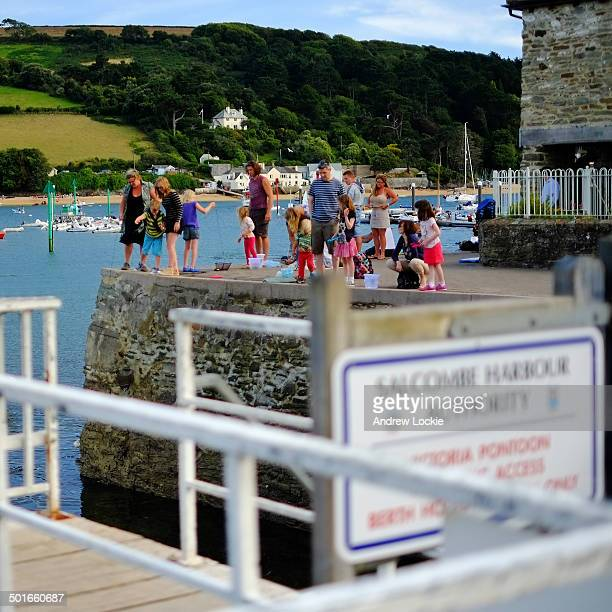 Parents and children seen fishing and crabbing from harbour walls, in the popular seaside town of Salcombe, on the English south coast, in Devon, UK.