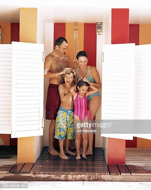 parents and children (5-9) showering at beach - frau unter dusche stock-fotos und bilder