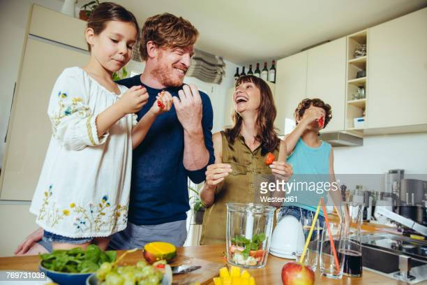 Parents and children tasting fruit for a smoothie