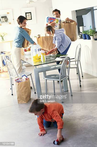 parents and children (5-9) unpacking groceries in kitchen - offloading stock pictures, royalty-free photos & images