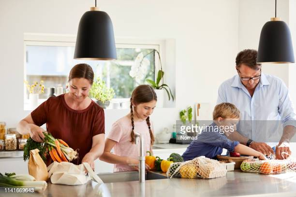 parents and children unpacking grocery in kitchen - danish food stock pictures, royalty-free photos & images