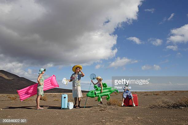 parents and children (6-10) with beach gear in desert - freaky couples stock photos and pictures